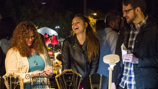 Artist Heidi Brunelle talks to Kiana Swatzell and Andrew Crittenden during First Friday on Roosevelt Street in downtown Phoenix on Friday, Dec. 4, 2015.