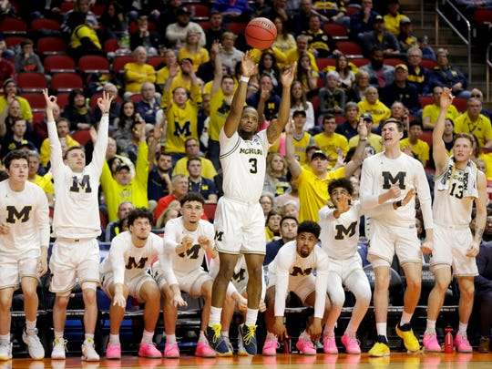Michigan's bench rises as Zavier Simpson shoots a 3-pointer in the second half against Montana.