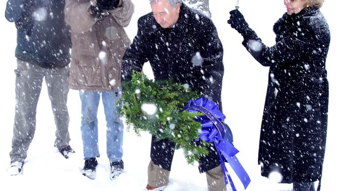 Bayard Marin, president of the Quaker Hill Historic Preservation Foundation, places a wreath Saturday at the grave of John Dickinson, surrounded by members of the foundation and Friends of the John Dickinson Mansion.