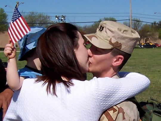 Rhonda Mathias kisses Capt. David Mathias after he returned home to the United States after a year's deployment in Iraq. Rhonda is holding their son Reuben.