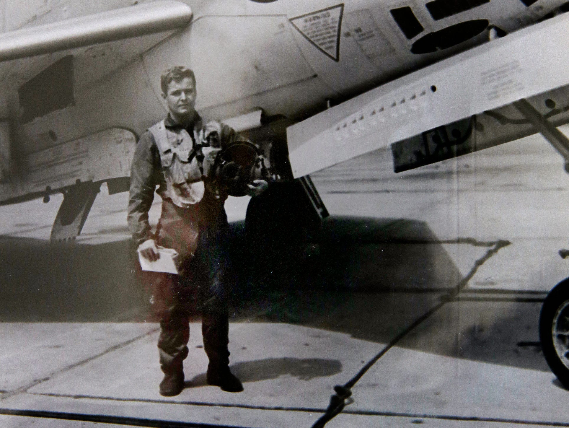 Jim Graham, pictured in front of a F3H, the plane he flew in the Navy, flips though photos on June 28, 2016.