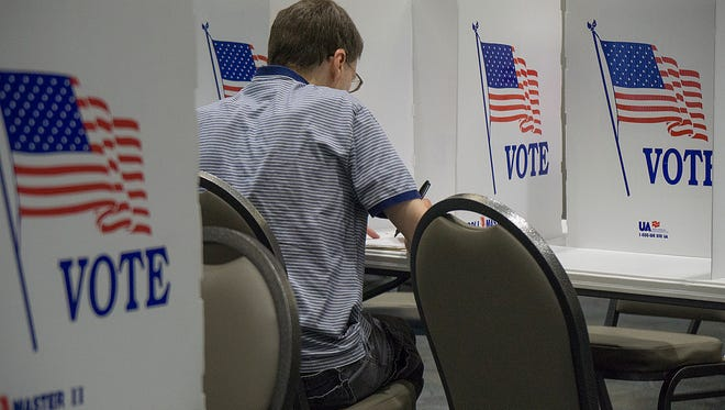 Voter Scott Ozga fills out his ballott. He was the 16th voter at Precinct 4 at 3:15 p.m.