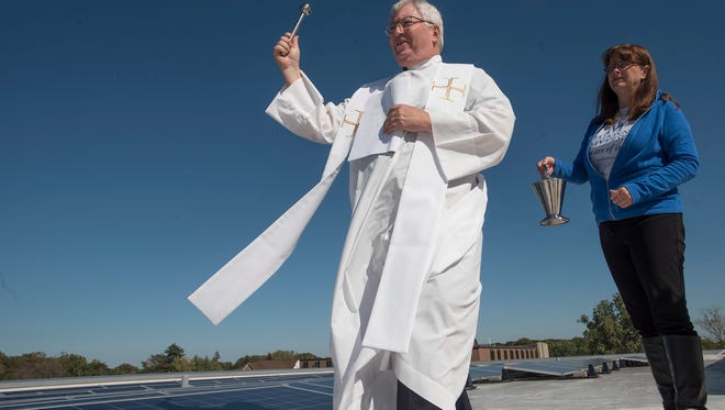 Father Charles Morris, accompanied by Karen Sanborn, blesses the solar panel installation.