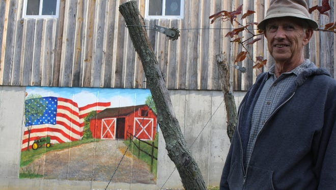 Linus Enzweiler stands by a row of Stueben grape vines in front of his family's Camp Springs Vineyard tasting room. The vineyard will be on the Campbell County Backroads Farm Tour on Saturday.
