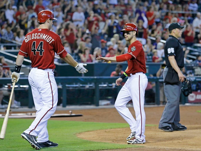 Diamondbacks first baseman Paul Goldschmidt (44) greets Ender Inciarte after he scored on a double by Diamondbacks left fielder David Peralta (6) in the 6th inning of their 3-2 win over the Chicago Cubs in their MLB game Sunday, July 20, 2014 in Phoenix, Ariz.