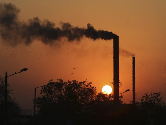 Birds fly past at sunset as smoke emits from a chimney at a factory in Ahmadabad, India, in this photo from 2014.