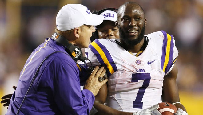 LSU Tigers head coach Les Miles hands  running back Leonard Fournette a game ball after breaking the single season rushing record during the second half of an NCAA college football game against Texas A&M in Baton Rouge, La., Saturday, Nov. 28, 2015. (AP Photo/Jonathan Bachman)
