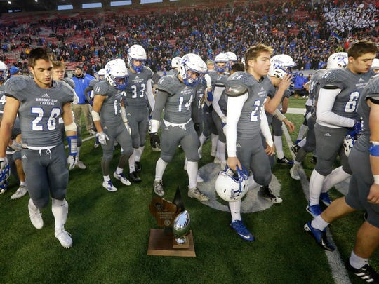 Brookfield Central players pass their runner-up trophy after the WIAA Division 2 state football championship game.