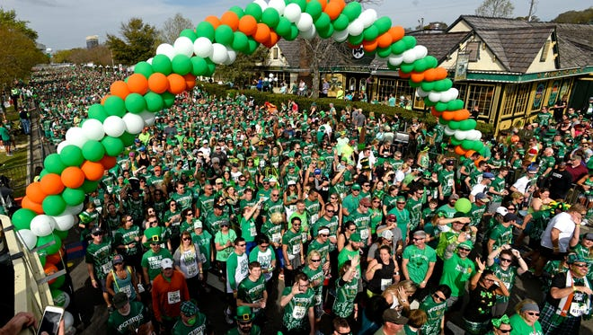 Runners make their way through the start line Saturday, March 10, 2018 during the 41st annual McGuire's St. Paddy's Day 5k.