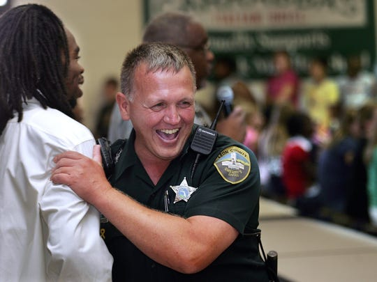 Swift Creek Middle School school resource officer Mike Peters jokes with a teacher inside the school's cafeteria during the hectic first day of school.