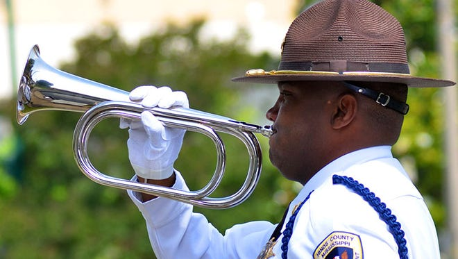 "A Hinds County Sheriff's deputy plays ""Taps"" during the 2014 Hinds County Memorial Day Service at the Hinds County Courthouse in Jackson."