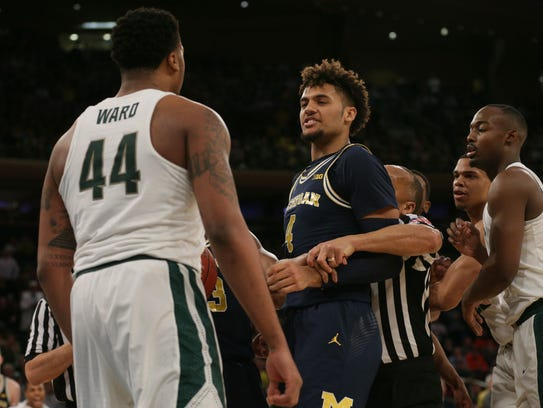 Michigan State forward Nick Ward, left, and Michigan forward Isaiah Livers react during the first half of their Big Ten tournament game on March 3, 2018.