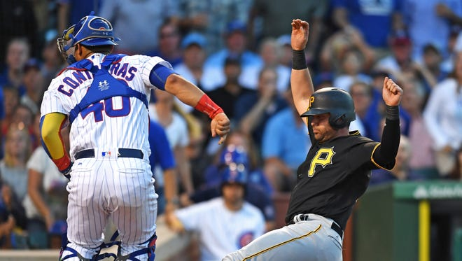 Pirates baserunner Francisco Cervelli, right, slides safely into home plate to score next to Cubs catcher Willson Contreras, left, in the sixth inning at Wrigley Field in Chicago.