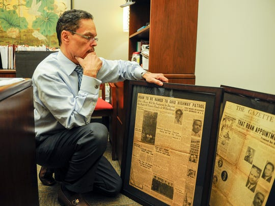Evansville banker Gary Roan looks through his collection of photos and newspaper clipping about his father Sanford Roan.