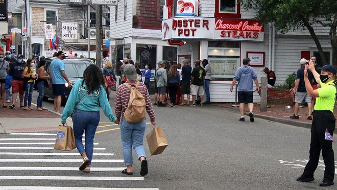 Provincetown community service officer Beth Berrigan directs pedestrian traffic at the intersection of Commercial and Standish streets this past holiday weekend. Despite the ongoing pandemic, tourists took to the Cape for the Fourth of July holiday.