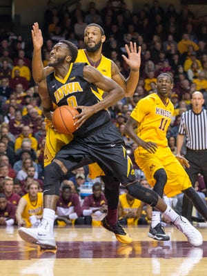 Iowa Hawkeyes center Gabriel Olaseni (0) drives to the basket past Minnesota Golden Gophers forward Maurice Walker (15) in the first half at Williams Arena.