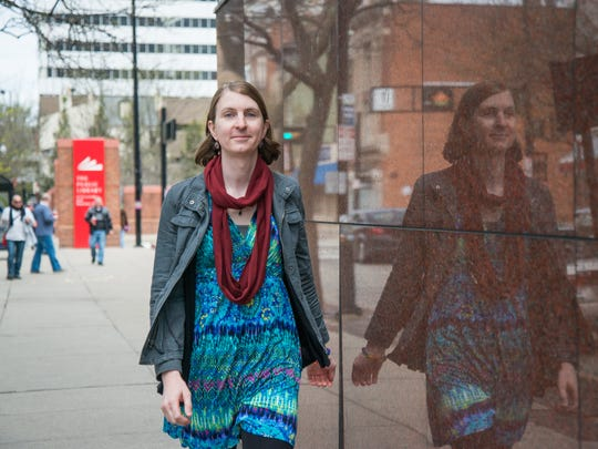 Rachel Dovel, who identifies as a transgender woman, is fighting to get insurance from her employers at the Cincinnati Library. Dovel poses for a photo outside the downtown Main Library Sunday April 10, 2016.
