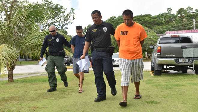 Vincent Leon Guerrero Unchangco, right, and Anthony Joshua Mendiola, left, are escorted to the Guam Police Department Hagatna precinct by Criminal Justice Strike Force officers upon their arrests on June 29.