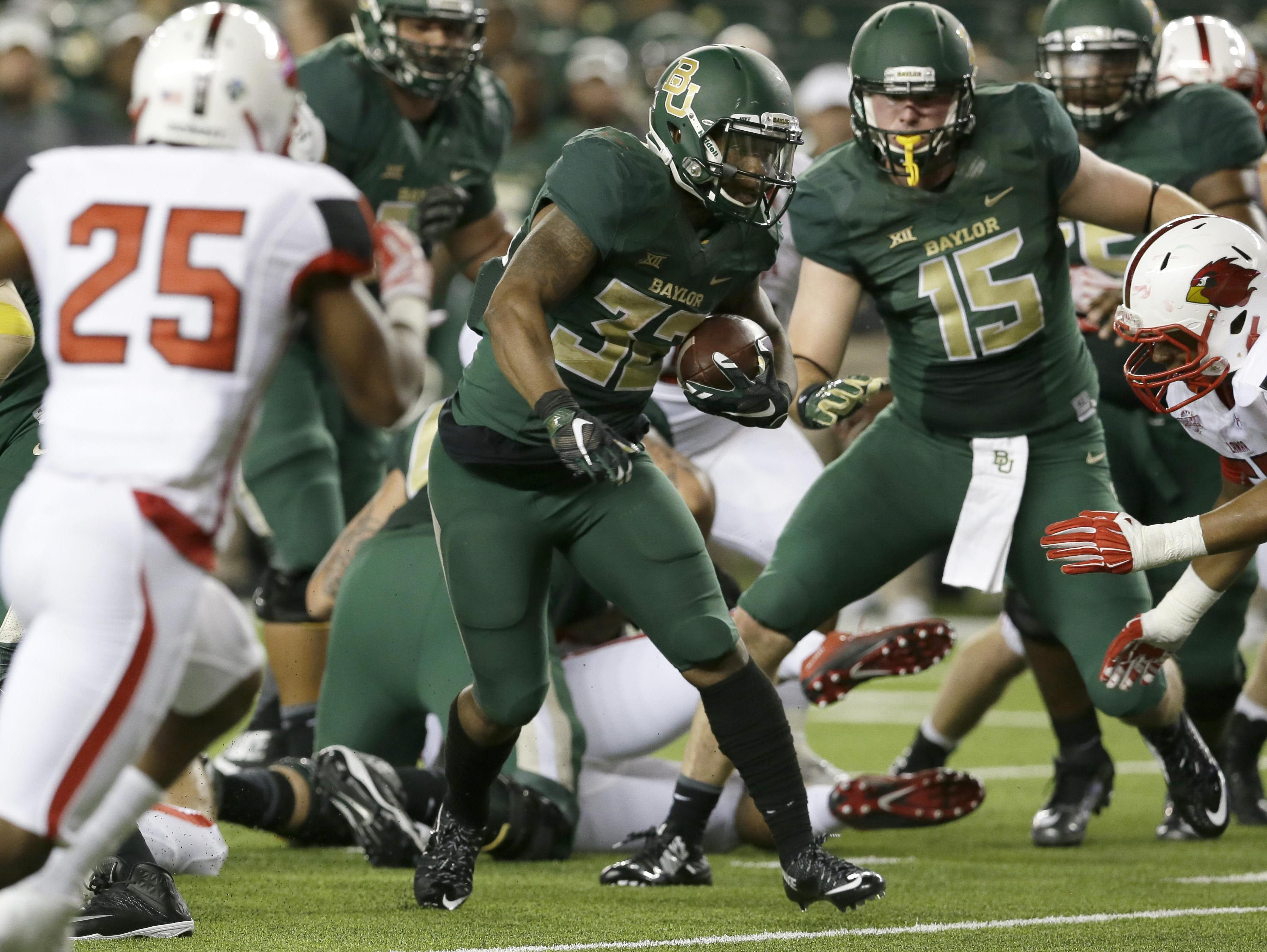 Baylor running back Shock Linwood (32) finds a hole to run though on his way to scoring a touchdown during the first half of an NCAA college football game against Lamar, Saturday, Sept. 12, 2015, in Waco, Texas. At left is Lamar defensive back Tommie Barrett (25) and at right is Baylor tight end Gus Penning (15). (AP Photo/LM Otero)