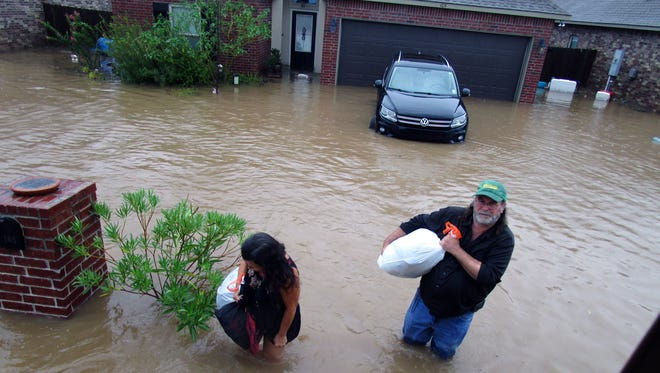 Theresa and Tony Yowell evacuate their home Aug. 12, 2016, in the Highland Ridge neighborhood of Youngsville, La.
