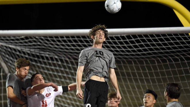 Northwest Rankin's Peyton Ratcliff goes high to head a throw-in near the Cougars' goal on Tuesday in an overtime win over Clinton. The Cougars look to win their first title since 2008 and fourth overall.