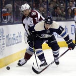 Columbus Blue Jackets' Cam Atkinson, right, and Colorado Avalanche's John Mitchell work for the puck during the second period of an NHL hockey game in Columbus, Ohio, Saturday, March 7, 2015.