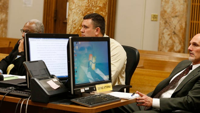 """Gerald """"Tig"""" Johnson, center, sits while a witness provides testimony during a hearing Friday, Feb. 26, 2016, at the Polk County Courthouse in Des Moines. Johnson, a girls' basketball coach and teacher at Roosevelt High School, is seeking to have sex abuse charges dismissed."""