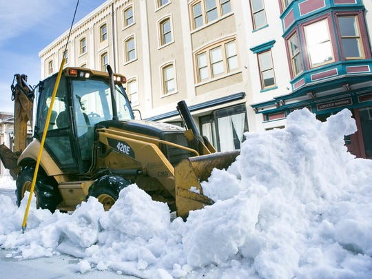 Wilmington road crews continue to clear snow along East 3rd Street at parking meter areas Thursday.