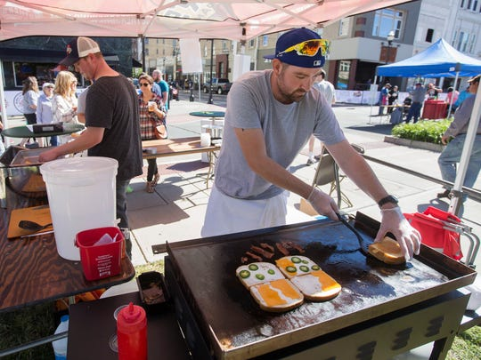Chris Buterbaugh, the kitchen manager at Druff's, prepares a pair of grilled cheese sandwiches at the Taste of SOMO & Oktoberfest Village event at Park Central Square on Saturday, October 8, 2016.