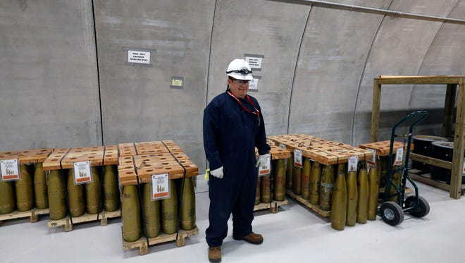 A munitions worker stands near inert simulated 155mm chemical munitions used for training inside a hardened hangar at the Pueblo Chemical Depot, east of Pueblo, in southern Colorado.