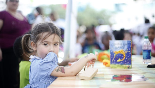 """Galicia Fiallos, 3, plays with a toy giraffe at the TCC Early Childhood Education booth, featuring the book """"Giraffes Can't Dance,"""" during Children's Week at the Capitol last year."""