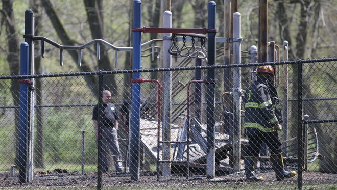 Fire fighters and investigators examine the scene of a suspicious playground fire that destroyed $60,000 worth of playground equipment at Francis Bellamy School 102, 9460 E. 36th Place in Indianapolis, Tuesday, April 18, 2017.
