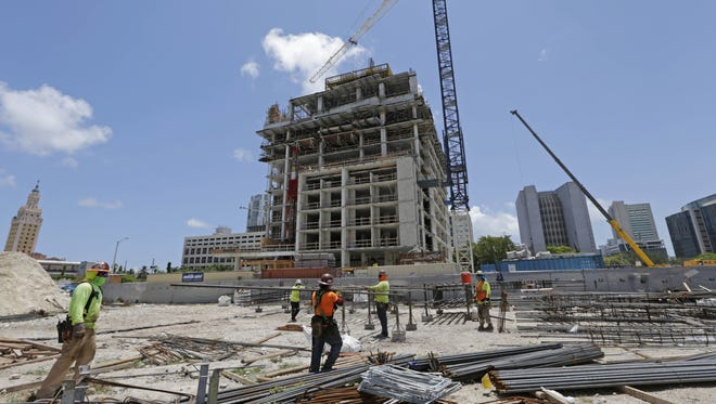 In this Thursday, May 4, 2017, photo, construction workers work on site of an apartment high rise in Miami. On Thursday, June 29, 2017, the Commerce Department issues the final estimate of how the U.S. economy performed in the January-March quarter.