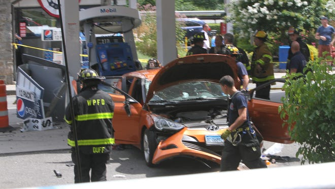 First responders check out a driver and his car that crashed into the service station on the Hutchinson River Parkway on Friday afternoon.