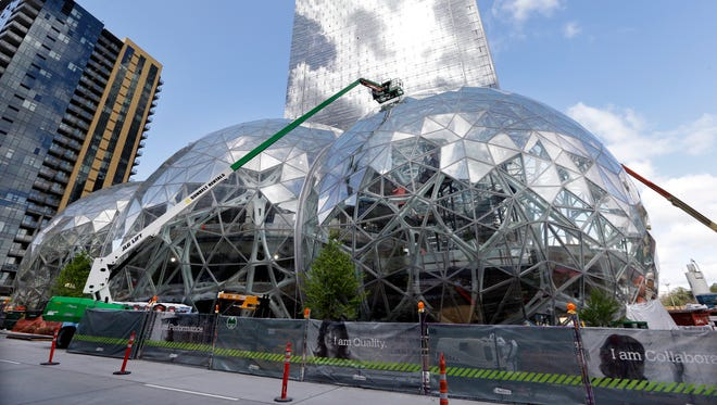 In this April 27, 2017, photo, construction continues on three large, glass-covered domes at Amazon.com's campus in downtown Seattle. Amazon will spend more than $5 billion to build a second headquarters in North America to house as many as 50,000 employees.