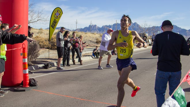 Dylan Villescas, 25, of Las Cruces crosses the finish line with a time of 26:31:5 in first place at Centennial High School for the 5-mile race in the Super Sunday Road Race VI on Feb. 4, 2018 in Las Cruces.