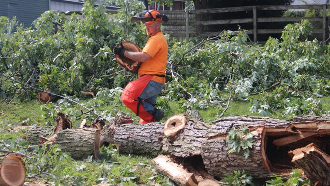 Preston Roberts, with Marion's Sanitation and Streets Department, clears a tree that fell Thursday night on Mark Street between North Prospect Street and North Main Street.