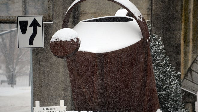 Mike Tripp/The News Leader Snow falls around the watering can sculpture along Greenville Avenue in Staunton. A winter storm blanketed the region with snow on Thursday, Dec. 16, 2010.