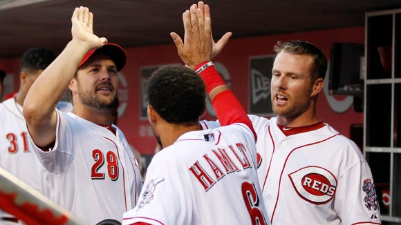 Reds center fielder Billy Hamilton (6) is congratulated by teammates Chris Heisey, left, and Zack Cozart during a game July 9.