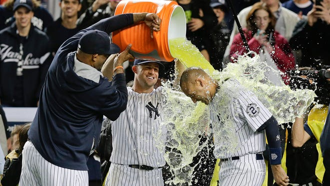 The Yankees' C.C. Sabathia, left, and Brett Gardner douse Derek Jeter after Jeter drove in the winning run against the Orioles in the ninth inning Thursday in New York. It was Jeter's final home game, and Tigers players took in the action from the clubhouse at Comerica Park.