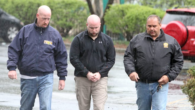 Brendan Cronin, 27, is escorted from the Pelham courthouse to the police station after his court appearance April 30. Cronin, a New York City police officer, was charged in connection with a shooting on a street in Pelham.