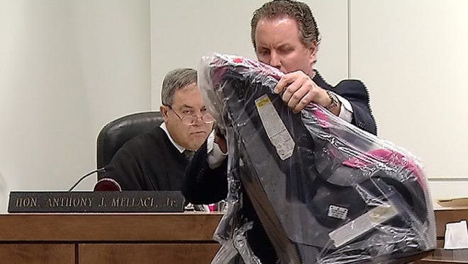 Marc LeMieux, first assistant Monmouth County prosecutor, holds the car seat and car jack that were used in the death of Tierra Morgan-Glover in Shark River Park in 2011.