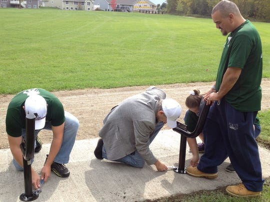 Volunteers work on one of five park benches installed at Mills Center Park in Howard.