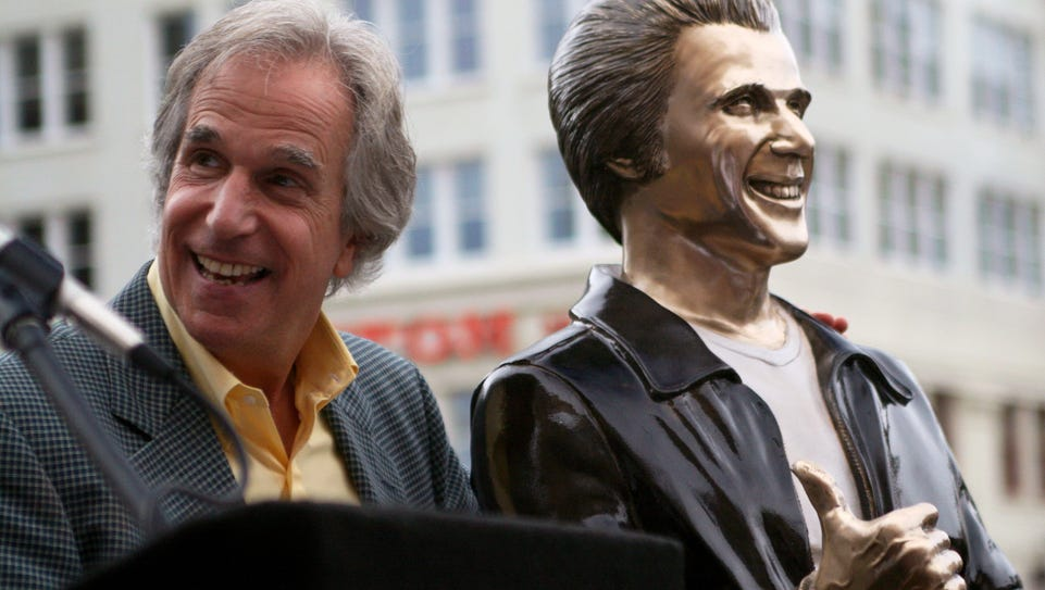 Actor Henry Winkler, left, poses with a bronze statue