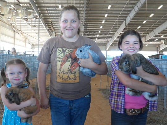 Holding rabbits on Sunday at the Rapides Parish Fair are (from left) sisters Ava Luno, 4, Adalynn Luno, 12, and Lily Basco, 10. The rabbits were among those in 4-H competition at the fair.