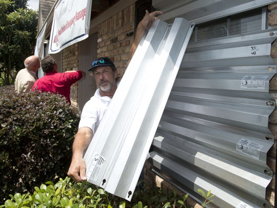 Emerald Coast Constructors Inc. employee Hilson Ragas puts up the window shutters on the 10,000th home strengthened by REBUILD Northwest Florida in 2014.