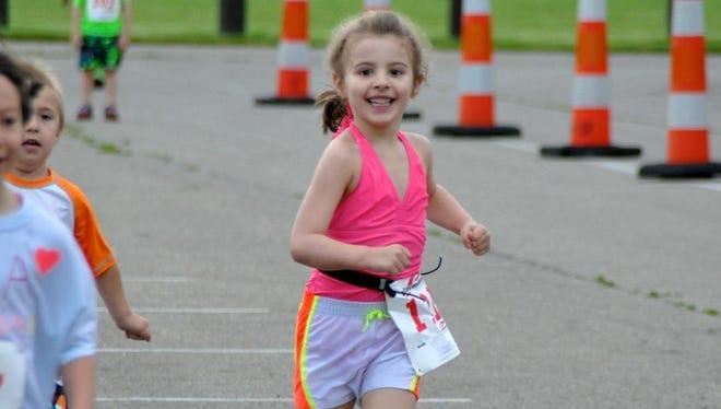 Lauren Sandborn, 4, finishes her first triathlon Saturday at Hawk Island Park in Lansing.