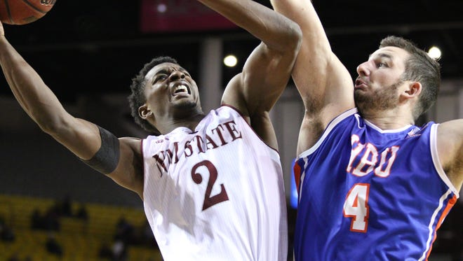 New Mexico State's Braxton Huggins looks for a shot against Houston Baptist's Cody Setler during the 2015-16 season opener Friday night at the Pan American Center.