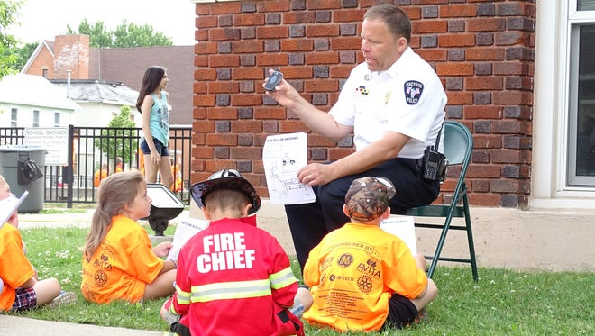 Retired Bucyrus Police Chief David Koepke teaches children how to call 911 during Safety Town in 2016.