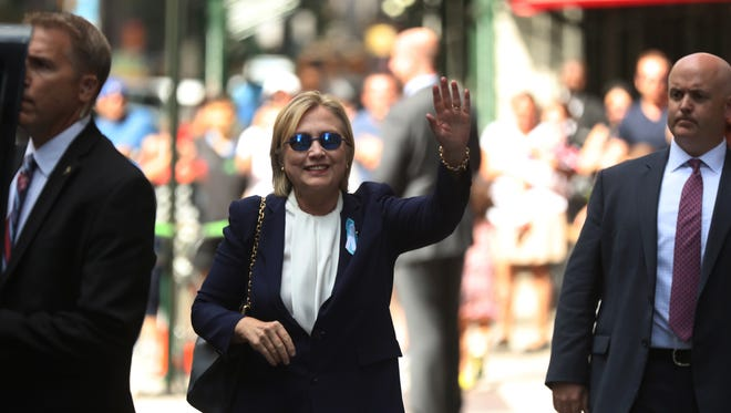"Democratic presidential candidate Hillary Clinton waves after leaving an apartment building Sunday, Sept. 11, 2016, in New York. Clinton's campaign said the Democratic presidential nominee left the 9/11 anniversary ceremony in New York early after feeling ""overheated."""